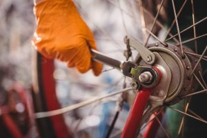 Close-up of mechanic repairing a bicycle in workshop